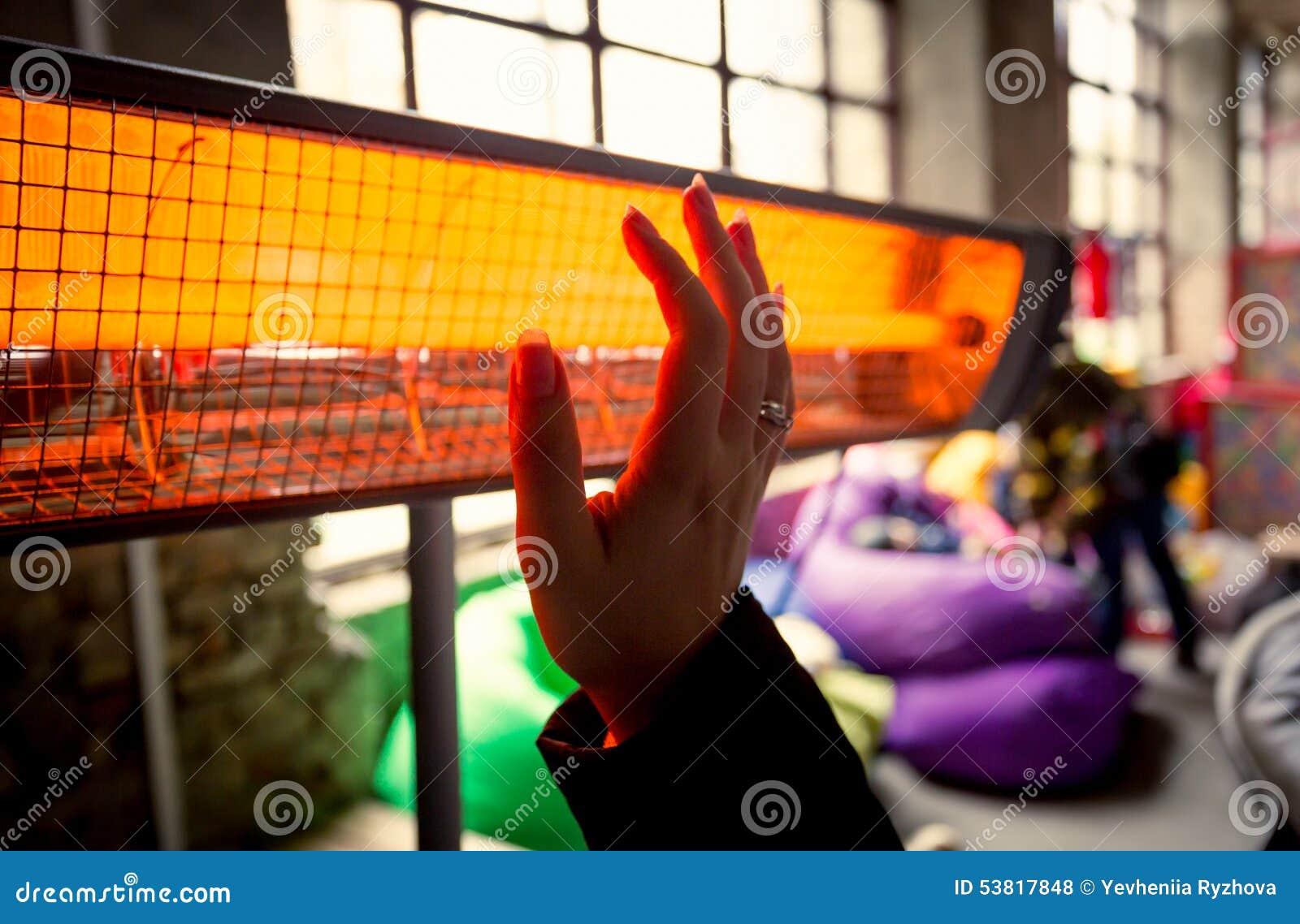 Closeup av kvinnavärmehänder på den infraröda värmeapparaten