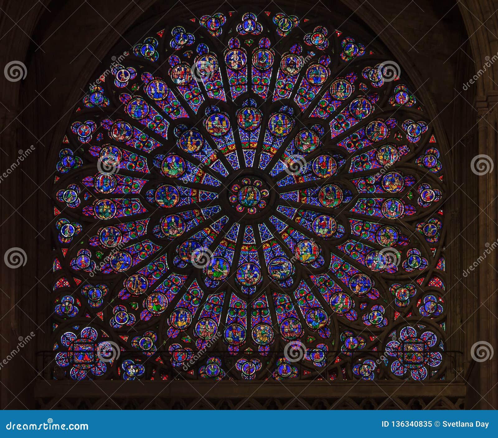 Closeup av målat glass av det äldsta rosa fönstret som installeras i 1225 i Notren Dame de Paris Cathedral i Paris Frankrike