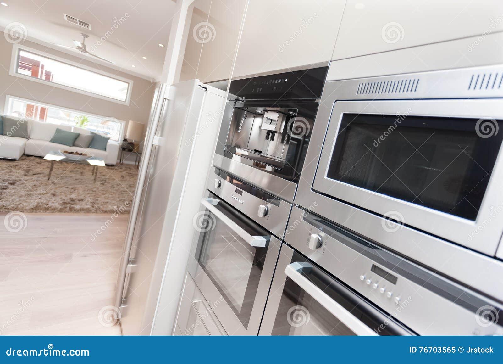 Closeup av moderna ugnar och ett kylskåp i den lyxiga kitcen