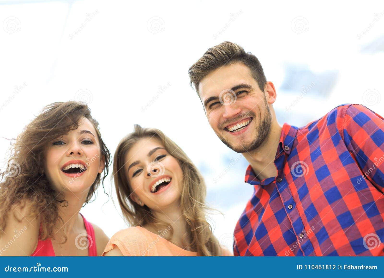 Closeup av tre ungdomarsom ler på vit bakgrund