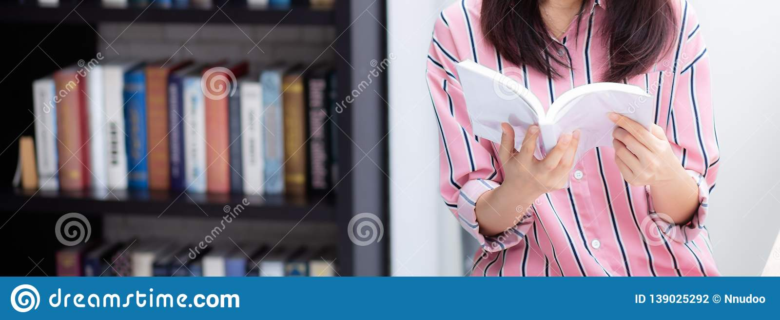 Closeup banner website young asian woman relax sitting reading book in living room at home