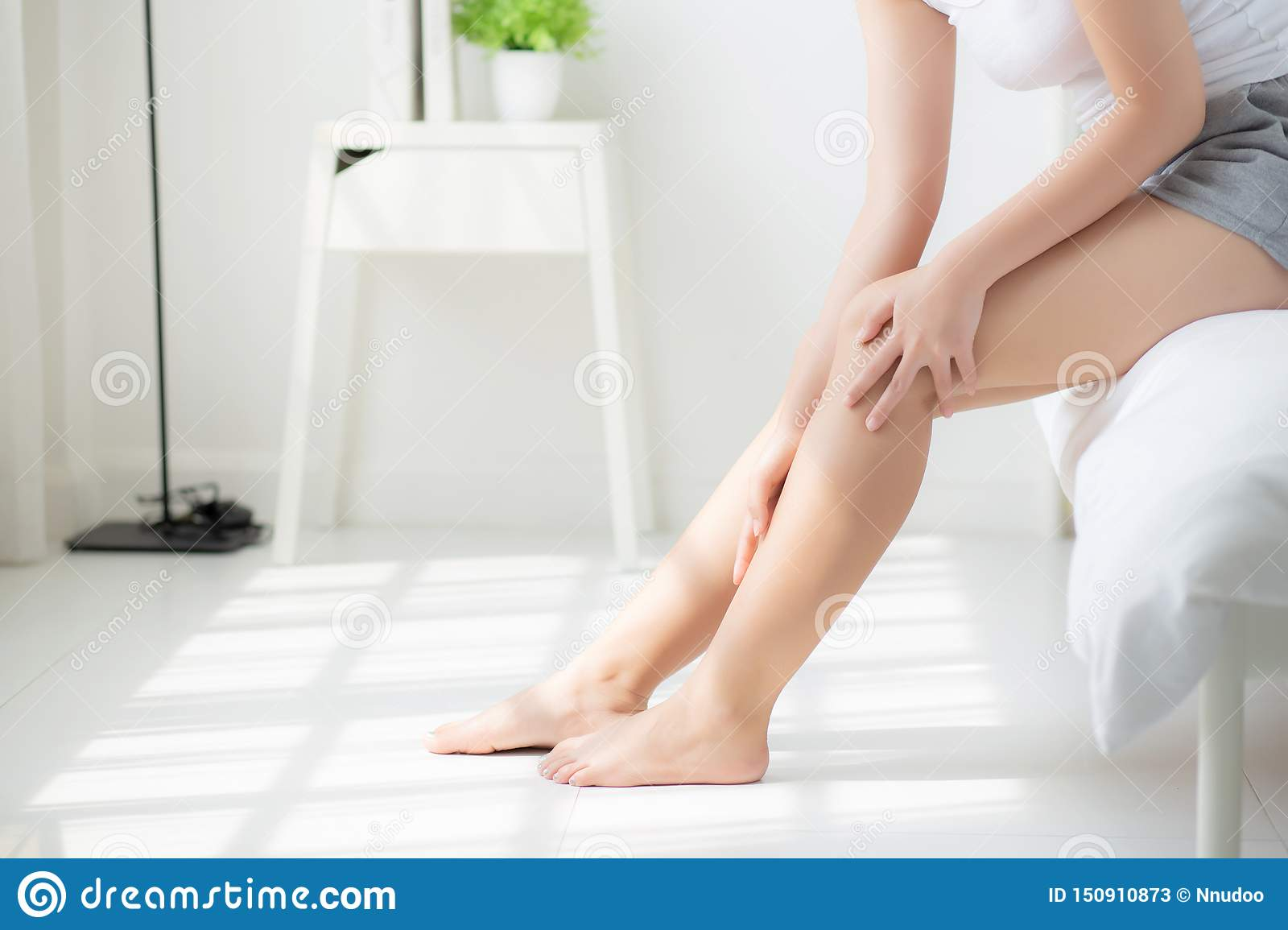 Woman Sitting On The Floor With Crossed Legs Stock Photo