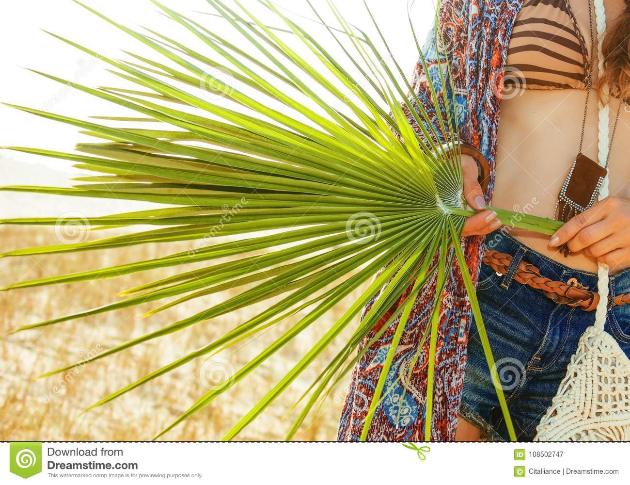 Closeup on big green tropical leaf in hand of bohemian chic