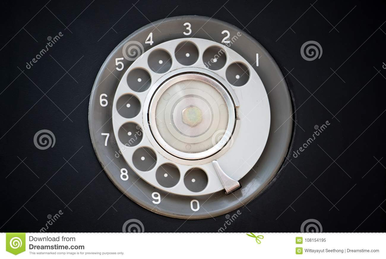 Closeup of black retro vintage telephone with rotary dialer or dial-pad.