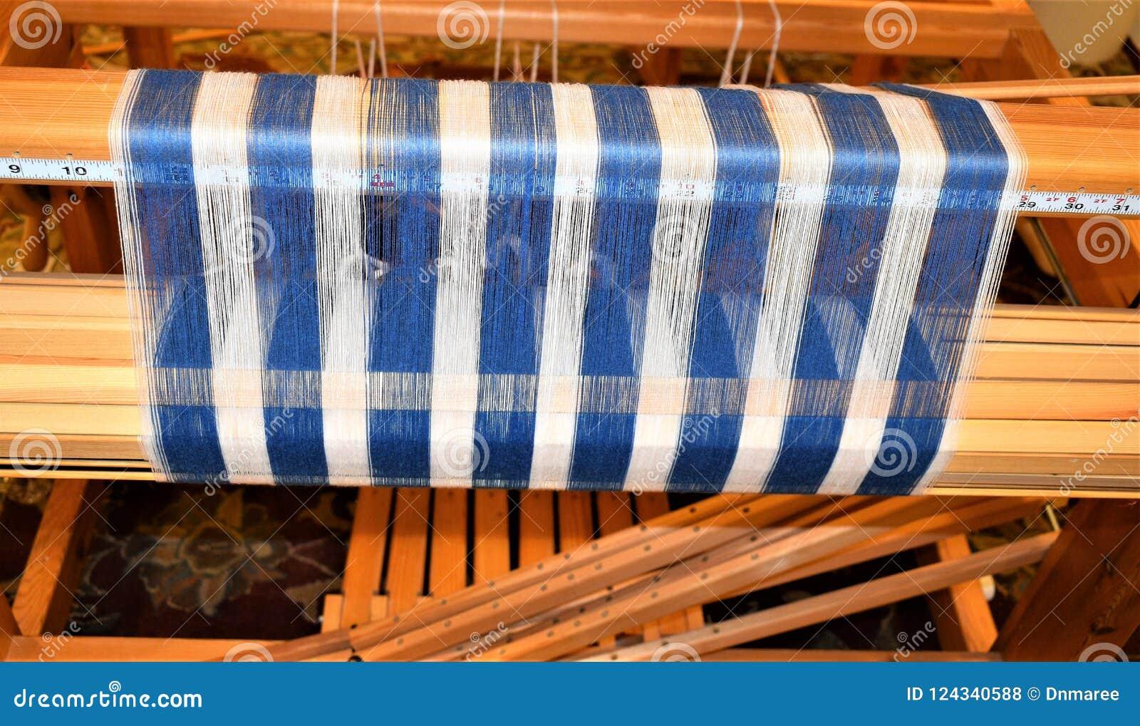 Closeup of Blue and white striped warp on back beam. Weaving. Handweaving. Textiles. Fiber.