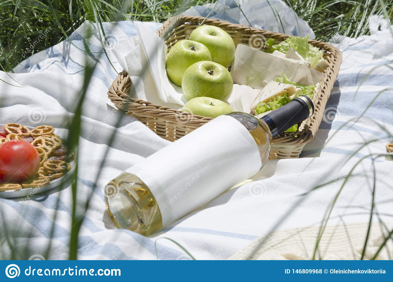 Closeup of bottle of white wine,juicy apples,delicious snacks.Picnic concept.Outdoor leisure.White wine as a great refreshing drin