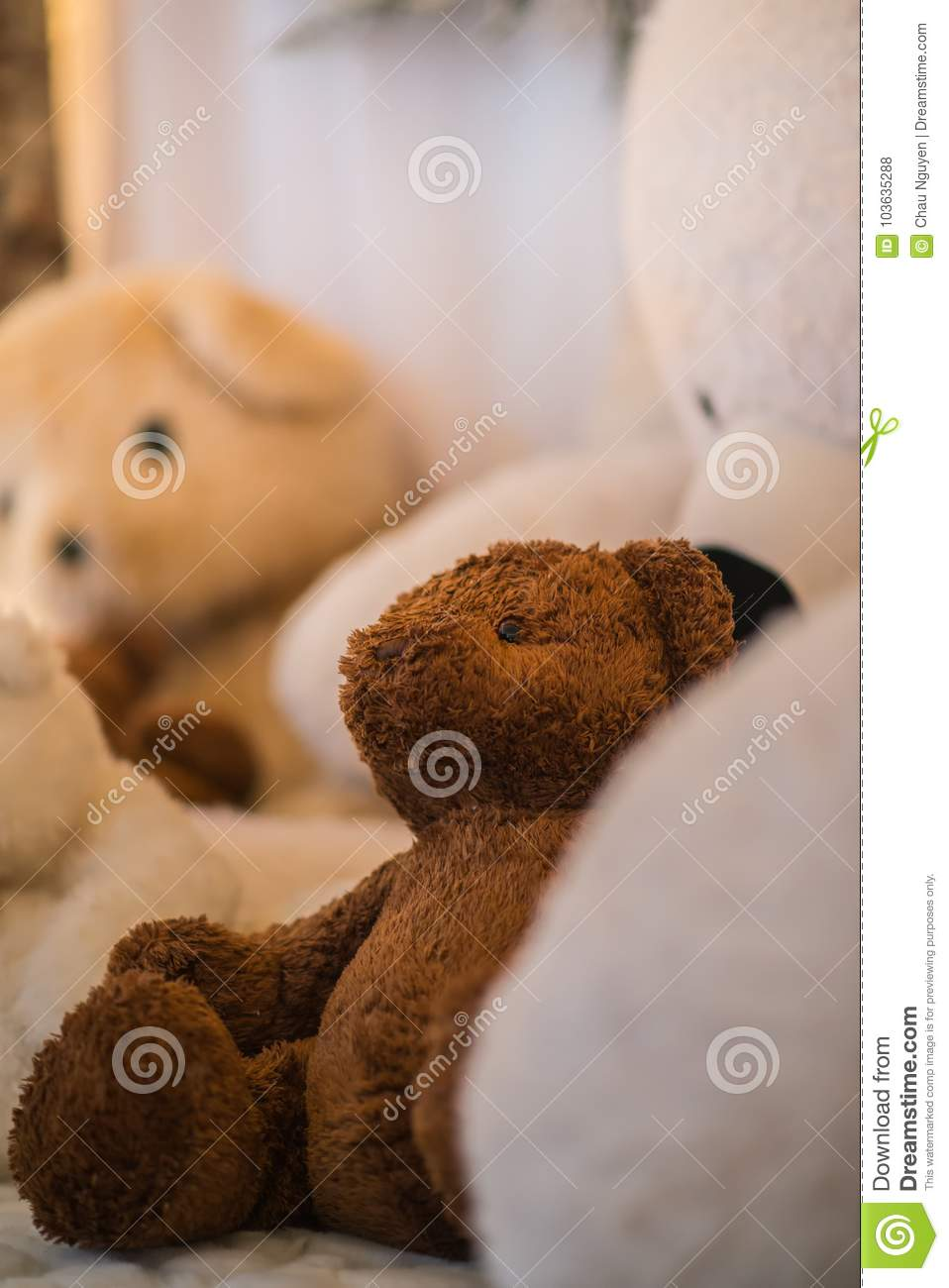 Closeup brown teddy bears lays inside white stuffted bears indoor under warmth lights. Cozy holidays