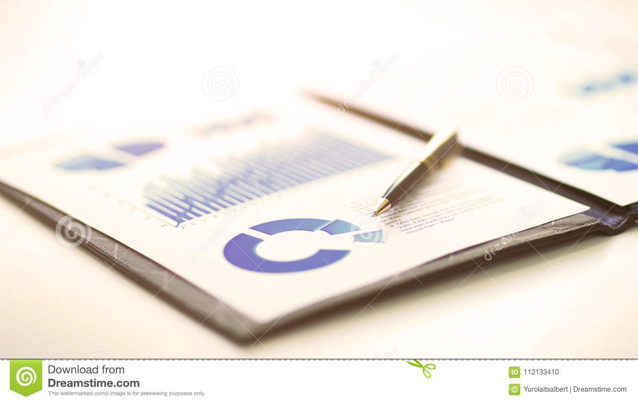 A closeup of a business financial chart with graphs. A pen is on top. Represent business expenses, growth or revenue.
