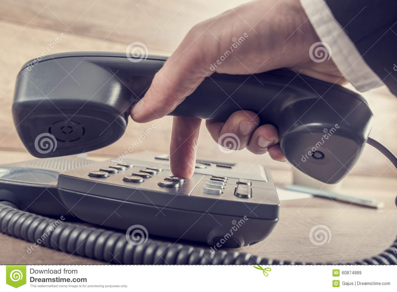 Closeup of businessman making a telephone call by dialing a phon
