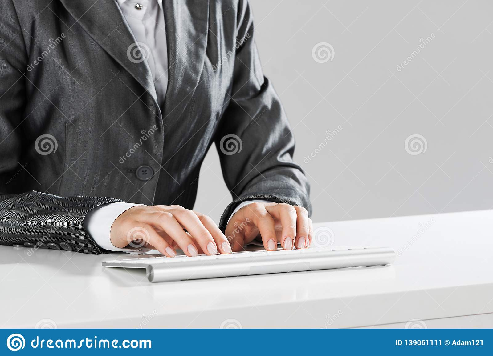 Closeup of businesswoman hand typing on keyboard with mouse on wood table