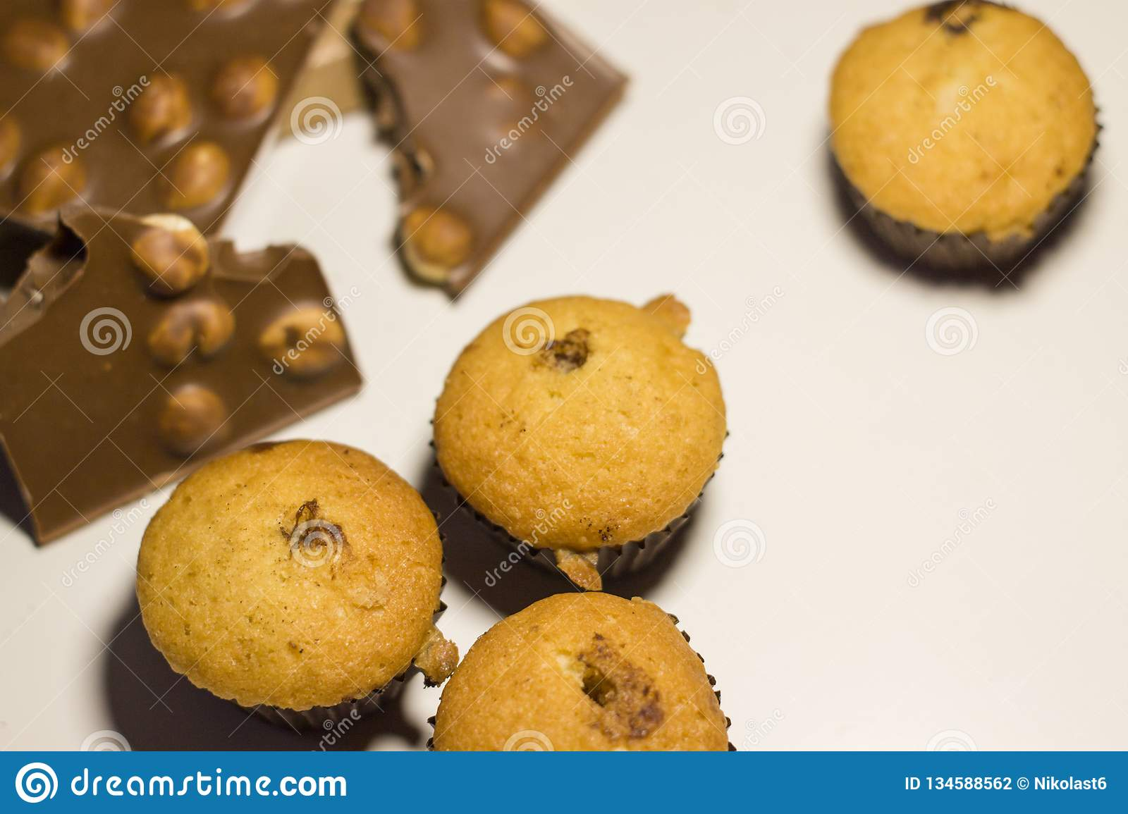 Closeup of sweets, chocolate with nuts and muffins on a white background.