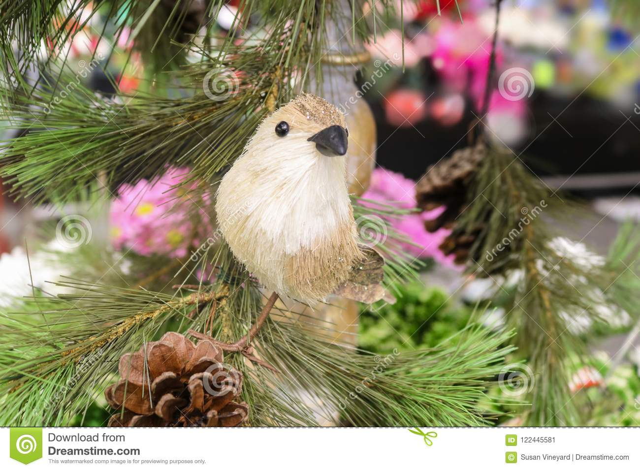 Closeup of Christmas straw bird perched on an artificial tree with pine cones with pink and colorful bokeh background