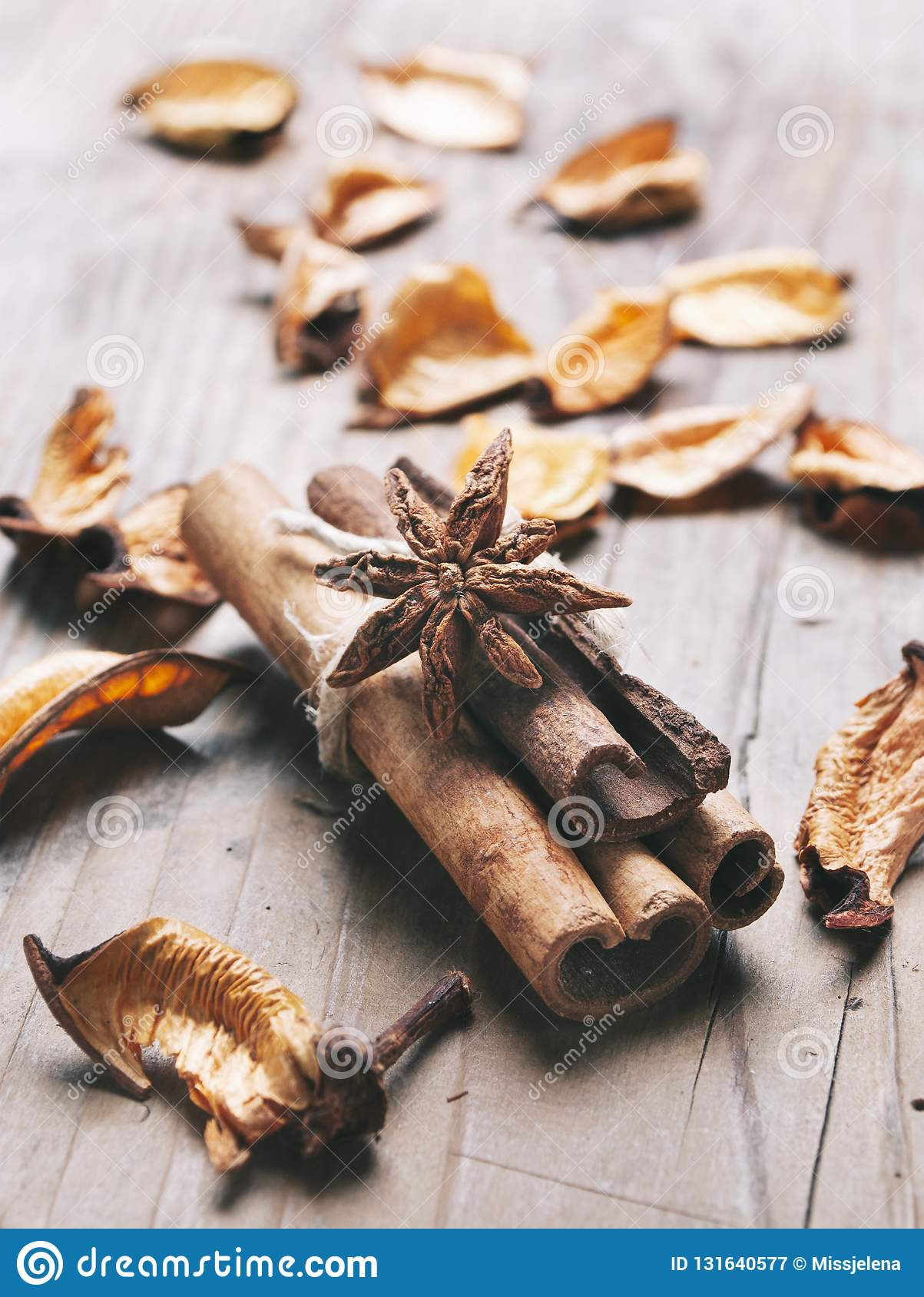 Closeup of cinnamon and anise star flavor with scented dry flower potpourri on vintage wooden table background. Zen relax