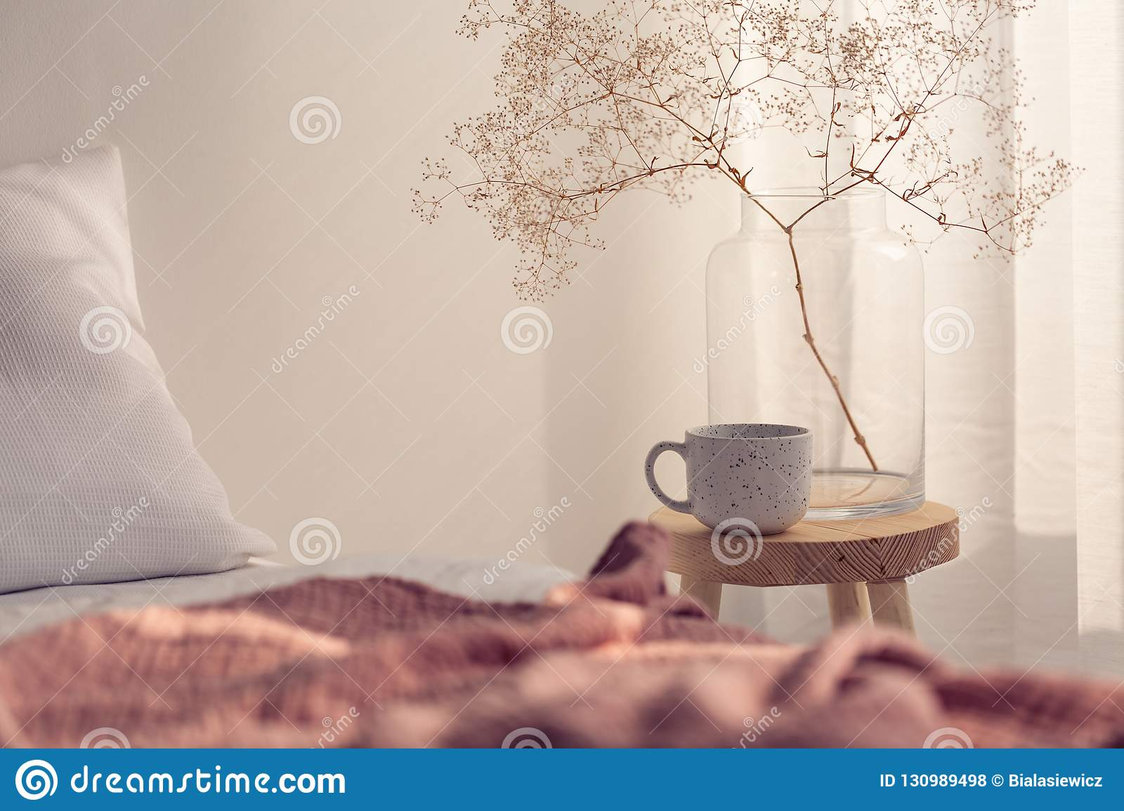Closeup of coffee cup and flower in glass vase on the bedside table of bright bedroom interior