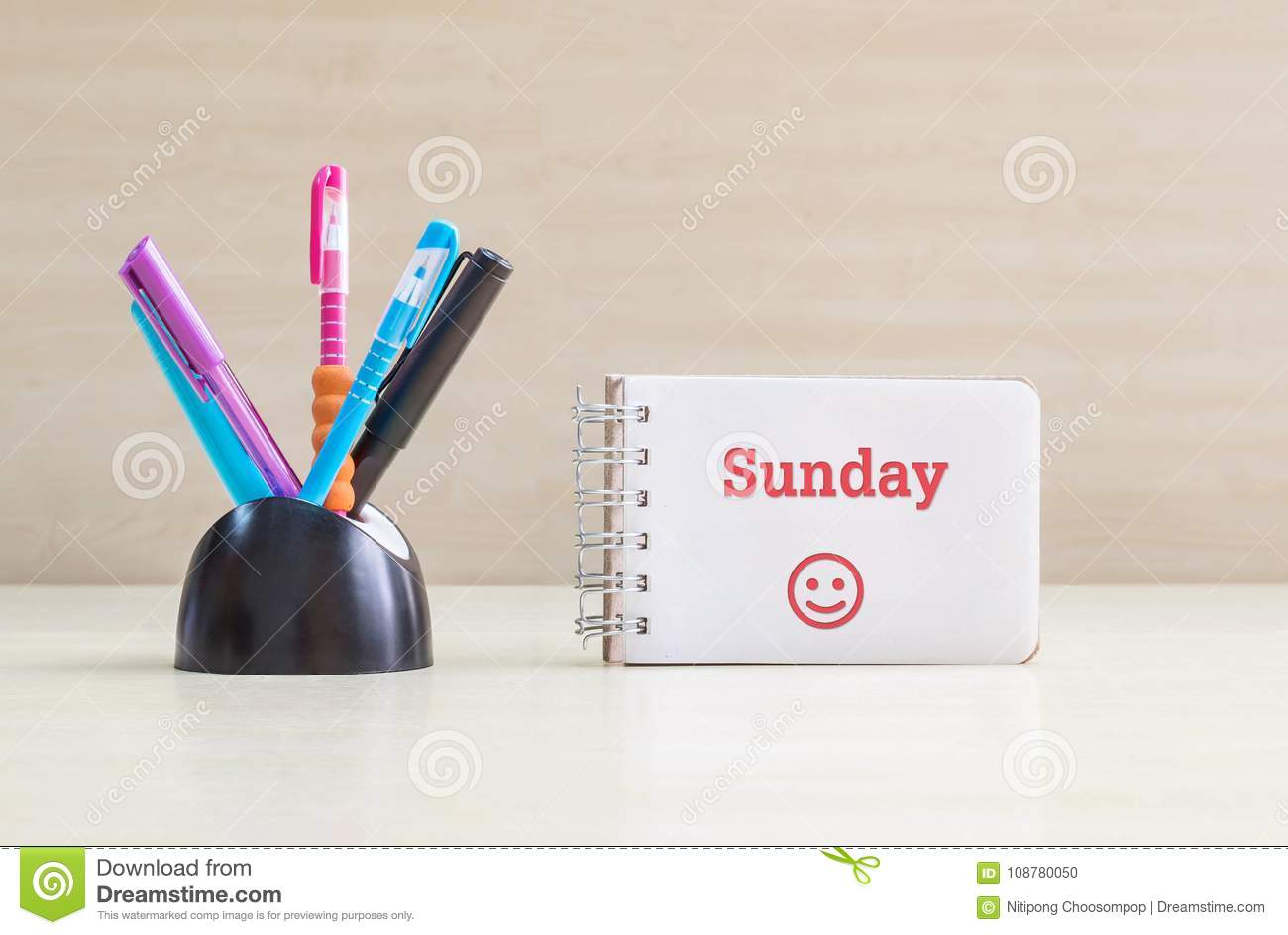 Closeup color pen with black ceramic desk tidy for pen and red sunday word in white page and happy face emotion at the note book o