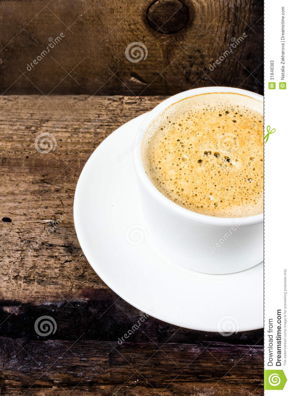 Closeup cup of espresso on old wooden table over grunge background, top view