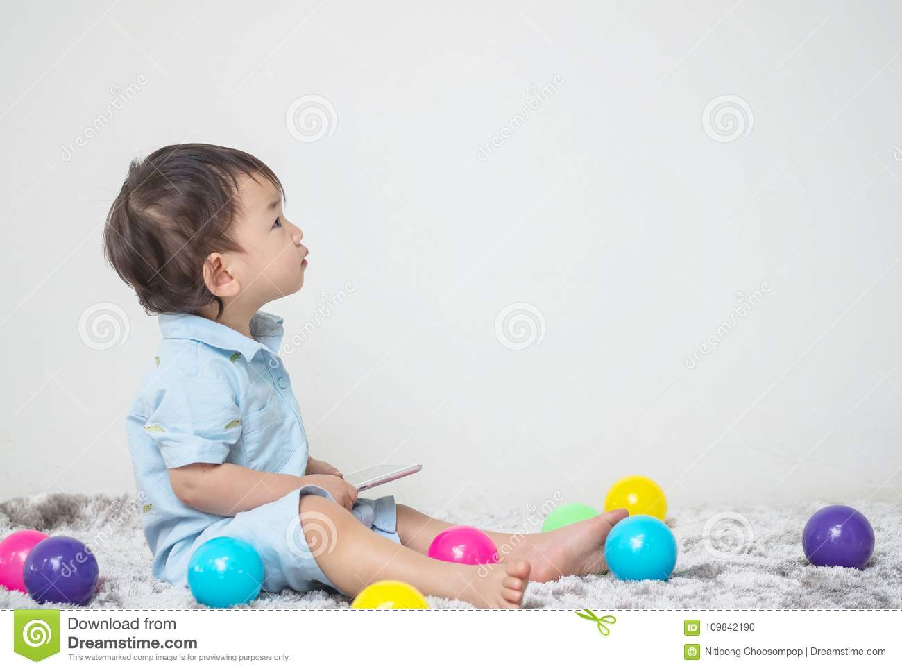 Closeup cute asian kid sitting and look at the space at white cement wall textured background on gray carpet with colorful ball