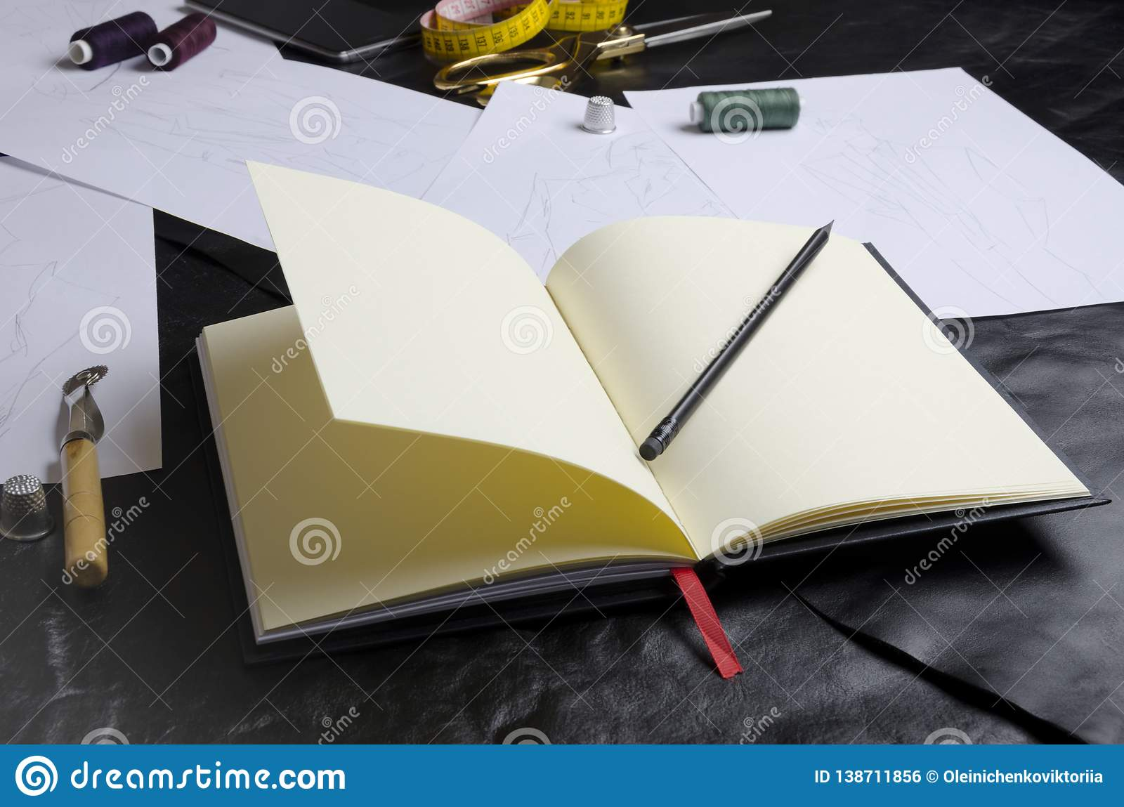 Closeup of designer`s notebook on table.Tools of designer during work.Concept of creating clothes collection