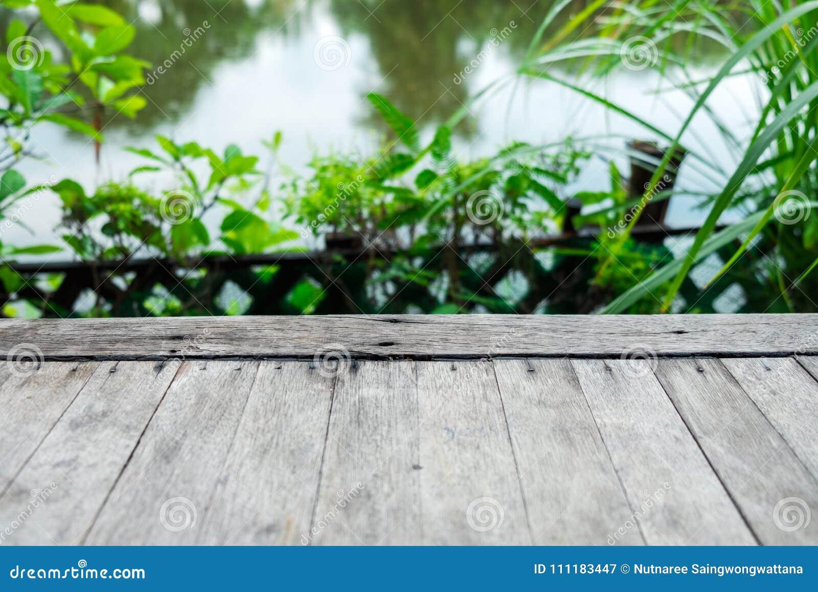 Closeup det gamla wood golvet bland naturen med trädet och floden är bac