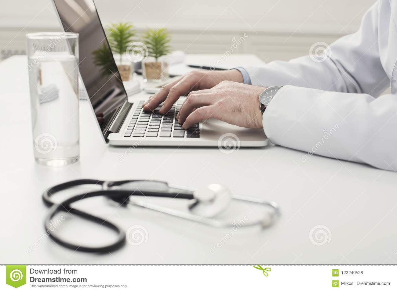 Closeup of doctor hands on laptop keyboard