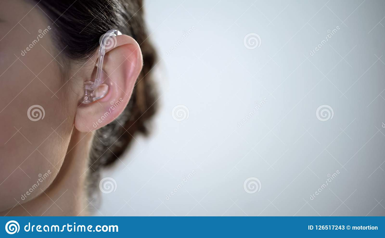 Closeup of ear with hearing aid, young deaf woman adjusting to environment