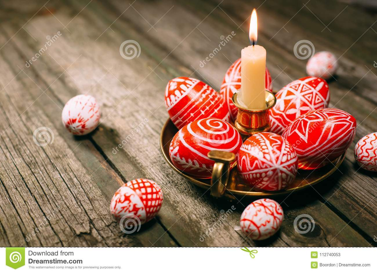 Closeup Easter red eggs with folk white pattern lay around on brass candlestick with burning candle and scattered eggs on rustic t