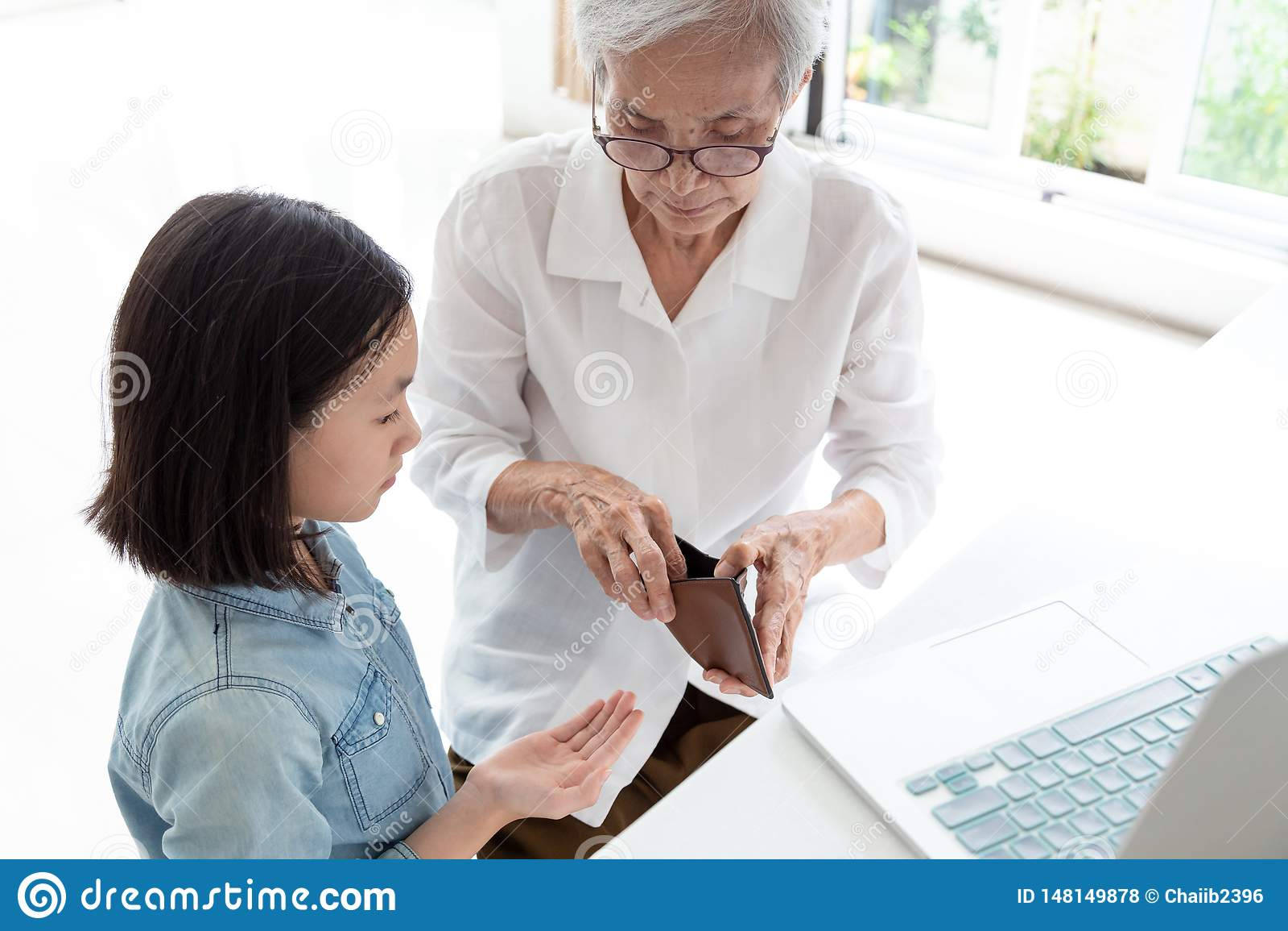 Closeup elderly woman hands open wallet,grandmother or guardian giving pocket money to granddaughter,asian little girl demanding