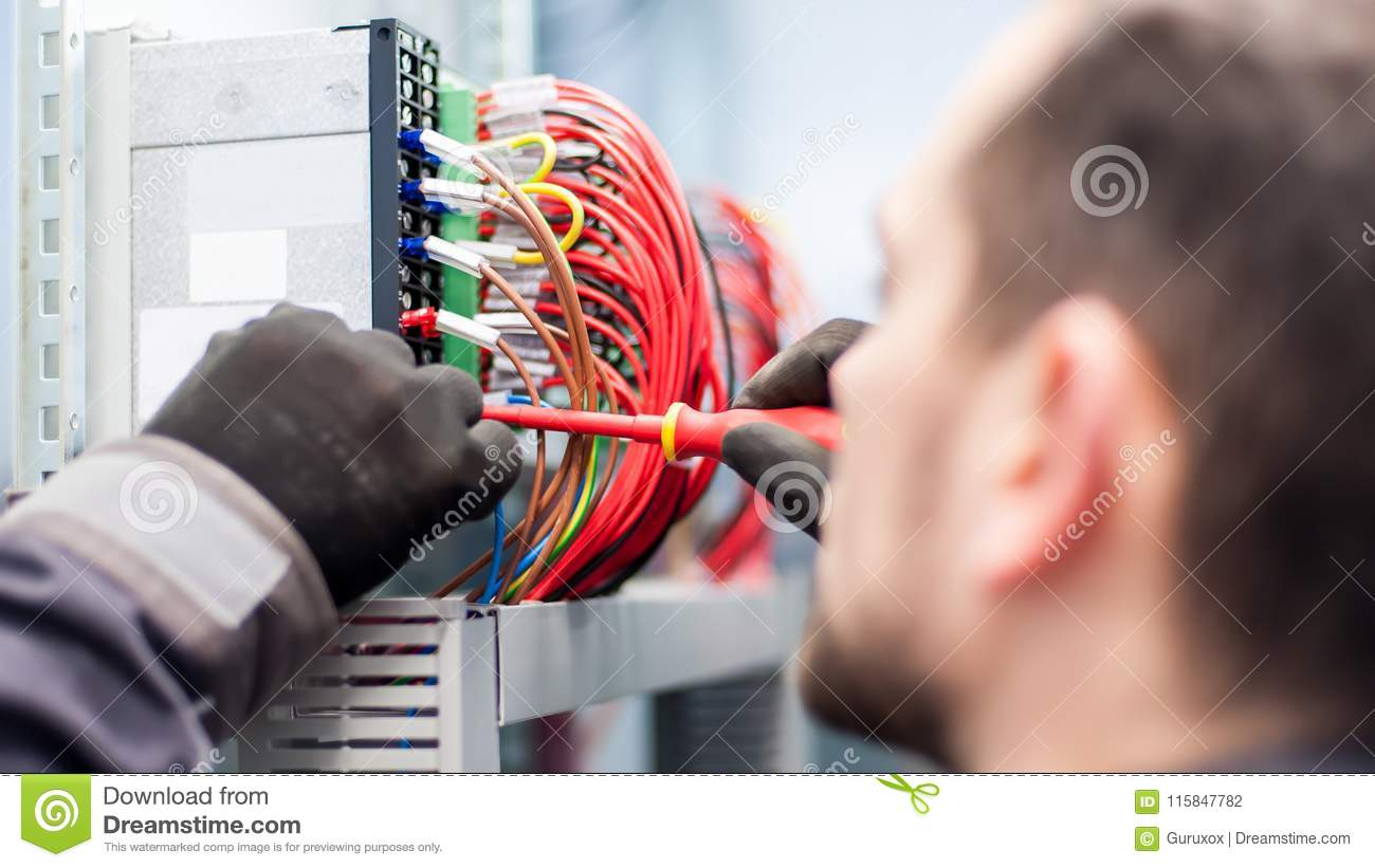 Closeup Of Electrician Engineer Works With Electric Cable Wires Fuse Box Switch Is Red Electrical Equipment