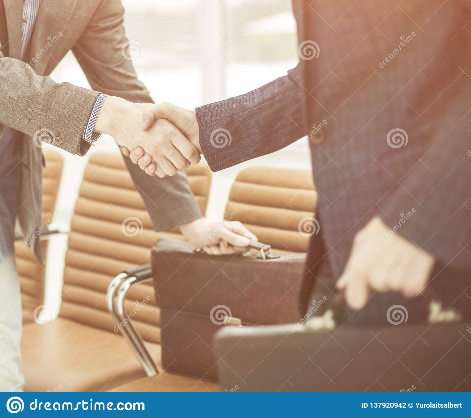 Employees of the company with briefcases shaking hands in the lobby of a modern office