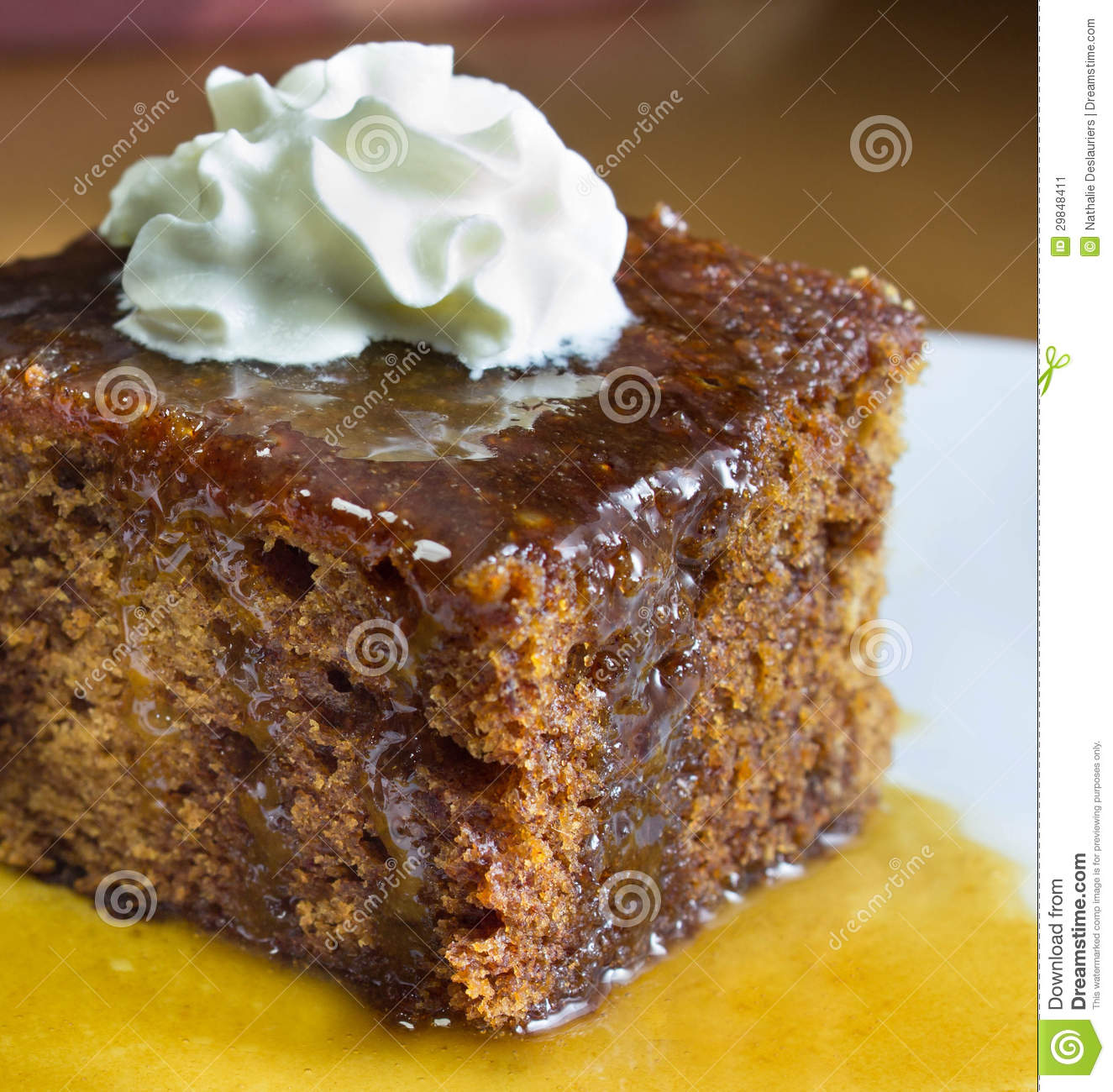 Closeup of english toffee pudding topped with vanilla whipped cream on ...