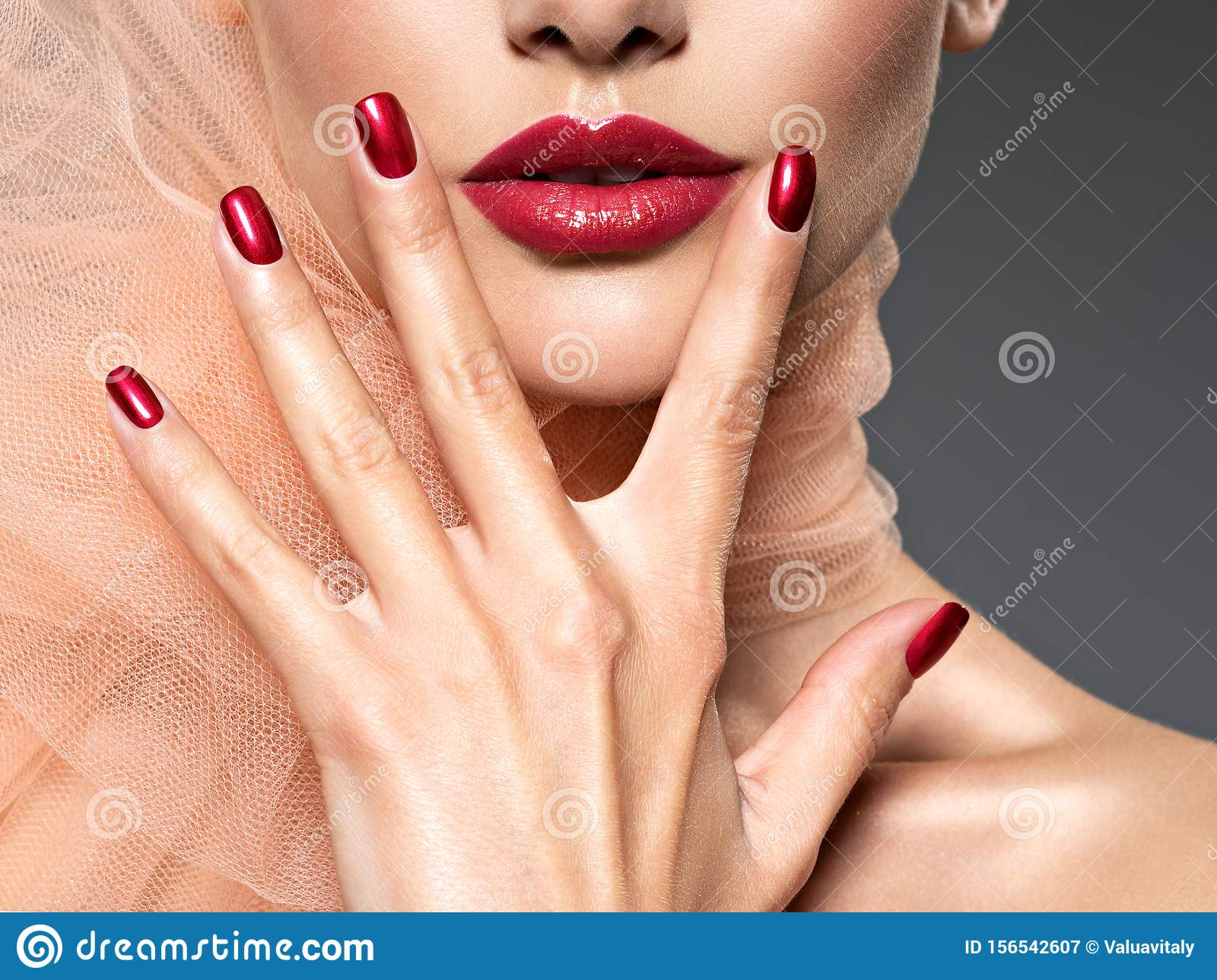 Closeup face of a woman with red nails and lips