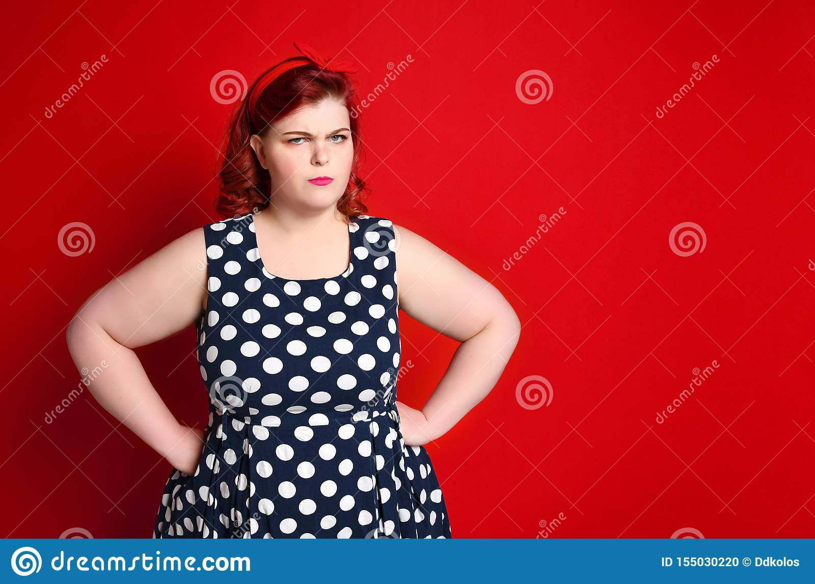 Closeup of a fat angry redhead woman holding her cheek by hand. pinup girl isolated .
