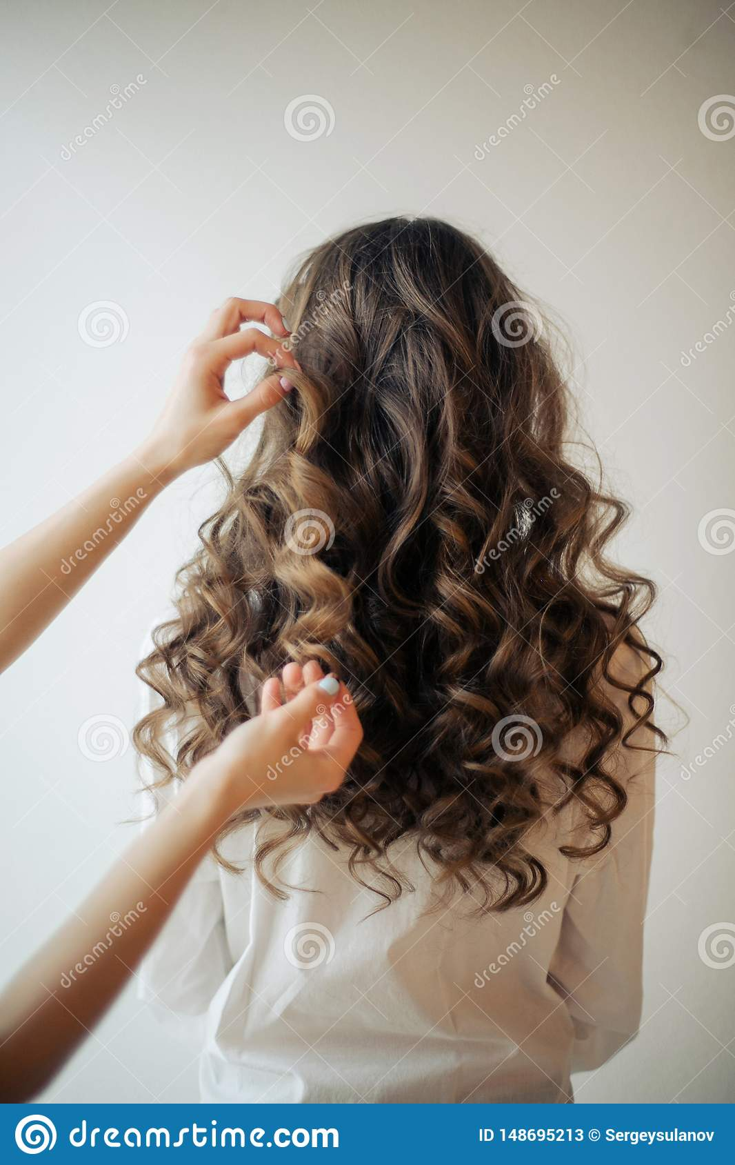 Closeup of female hands of hairdresser or coiffeur makes hairstyle