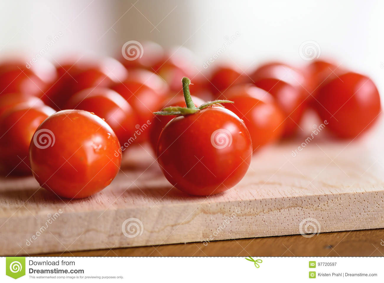 Closeup of fresh homegrown cherry tomatoes on a wooden cutting board