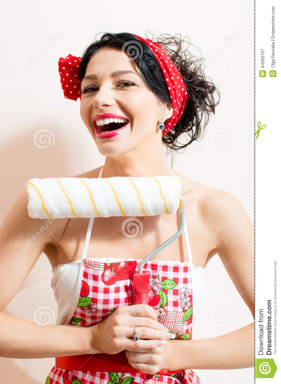 Closeup on funny brunette pinup pretty girl holding paint bolster, having good time & fun looking at camera and laughing