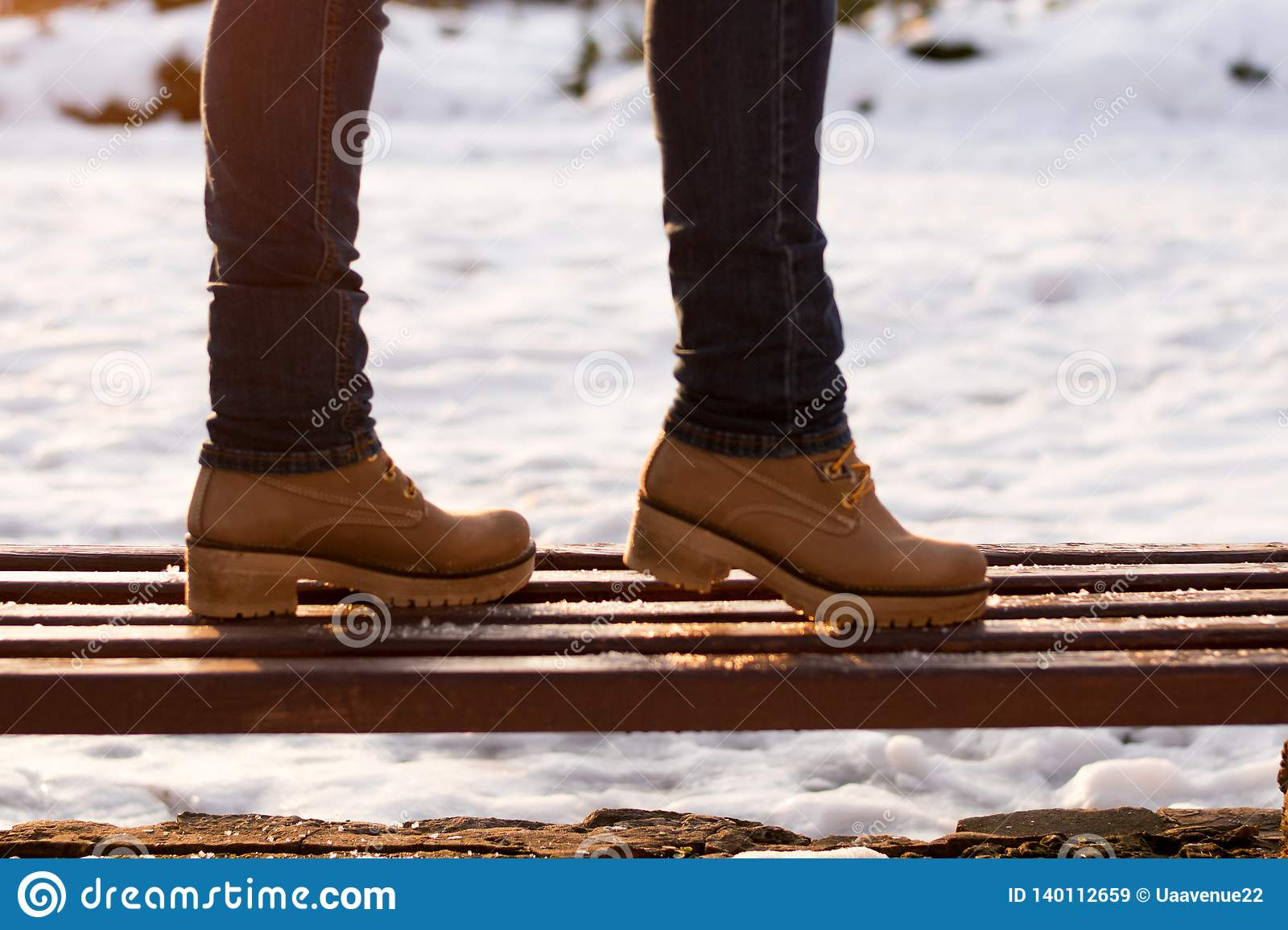Closeup girls legs on bench in winter sunny day on blurred background. Romantic walking in park in casual style outerwear. Concept