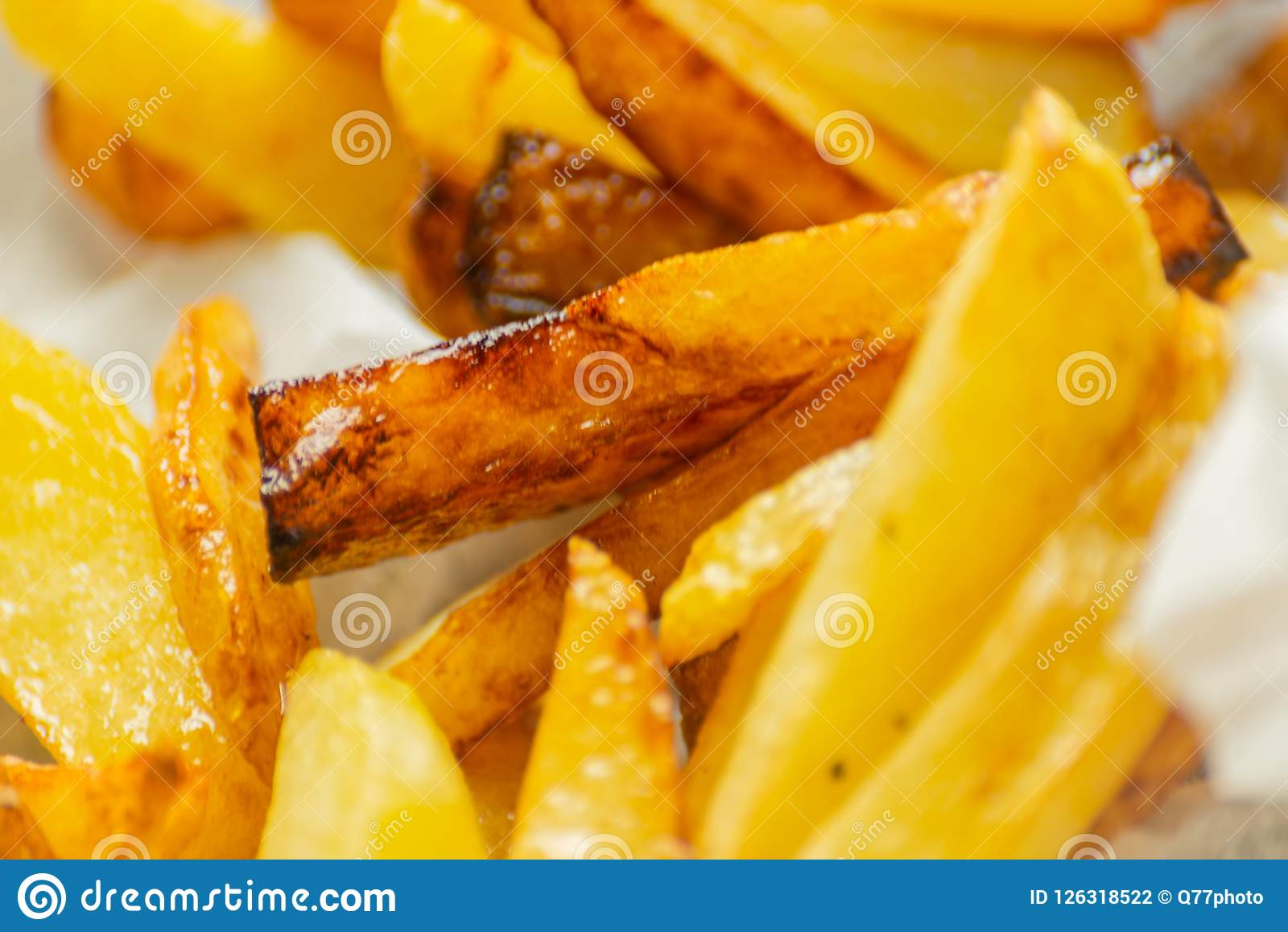 Closeup of golden fries prepared from fresh potatoes, greasy but