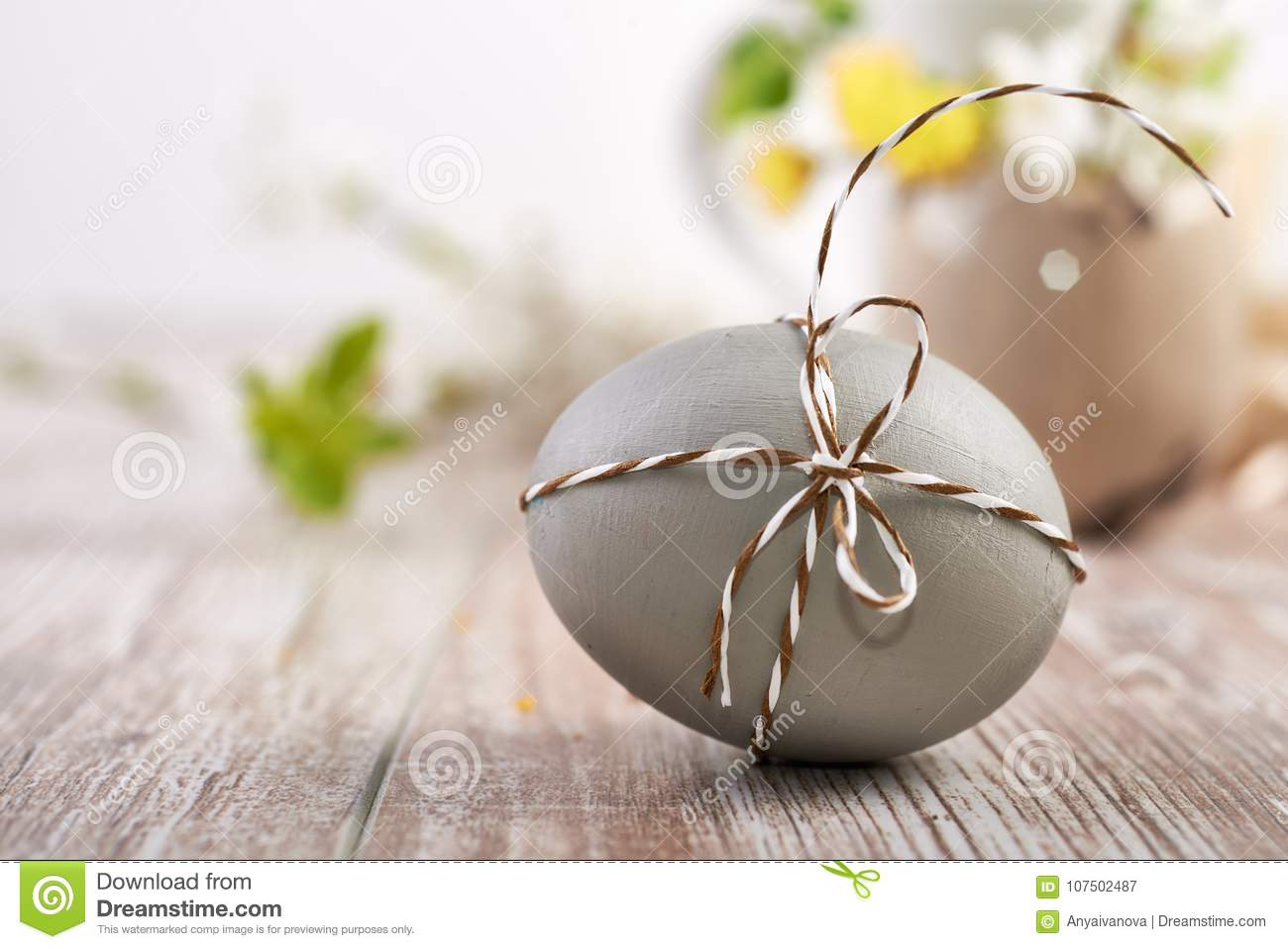 Closeup on grey Easter egg tied with checkered cord on wood