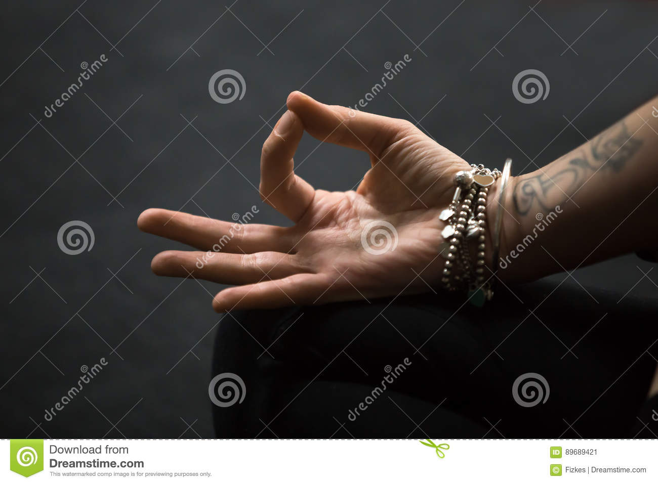 Closeup of gyan mudra spiritual gesture performed with female close up of dhyana gyan or jnana mudra spiritual hand gesture performed with yogi female fingers tattoo and wrist bracelets woman meditating on black mat thecheapjerseys Choice Image