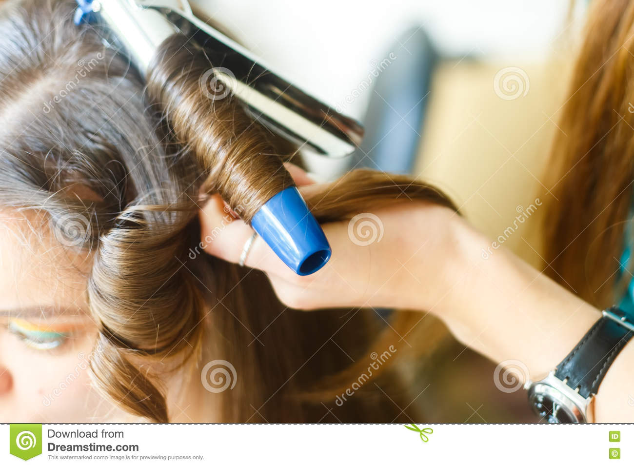 Closeup of hairdresser doing the styling for a festive evening of wedding hairstyles woman with long black hair