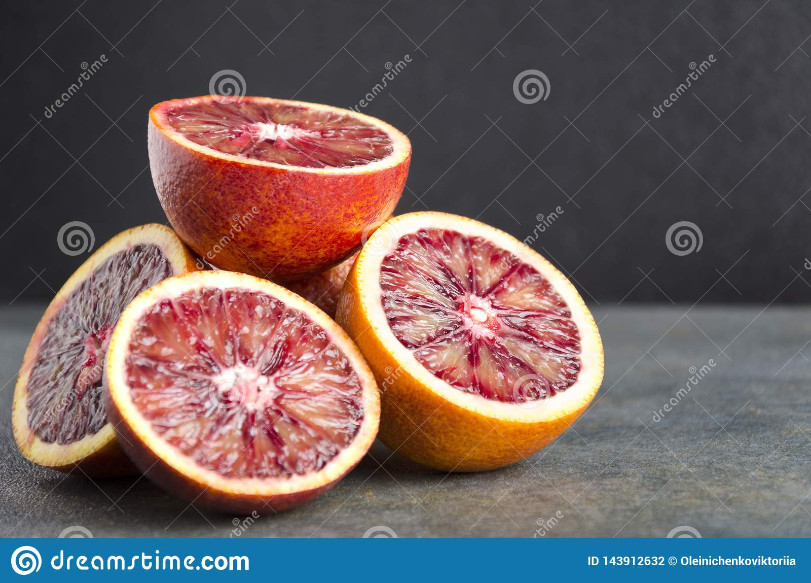 Closeup of halves of bloody oranges on grey table against black background.Fresh sicilian oranges