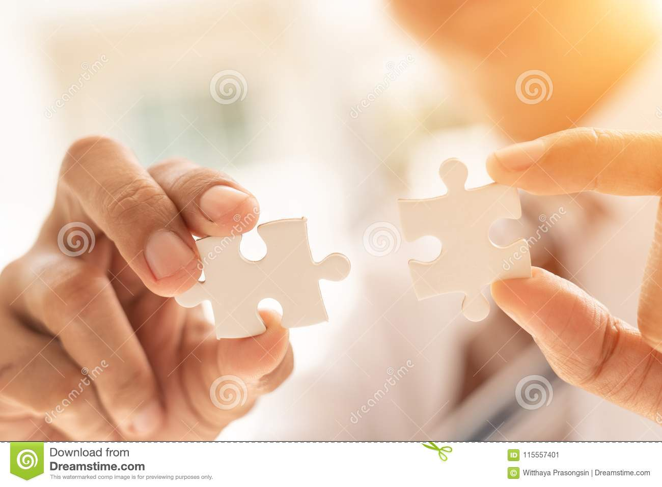 B Stock Solutions closeup hand of connecting jigsaw puzzle with sunlight
