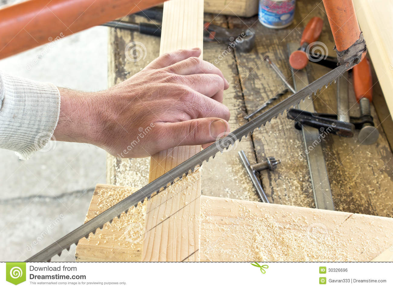 Closeup of hand cutting wood with a saw stock photo