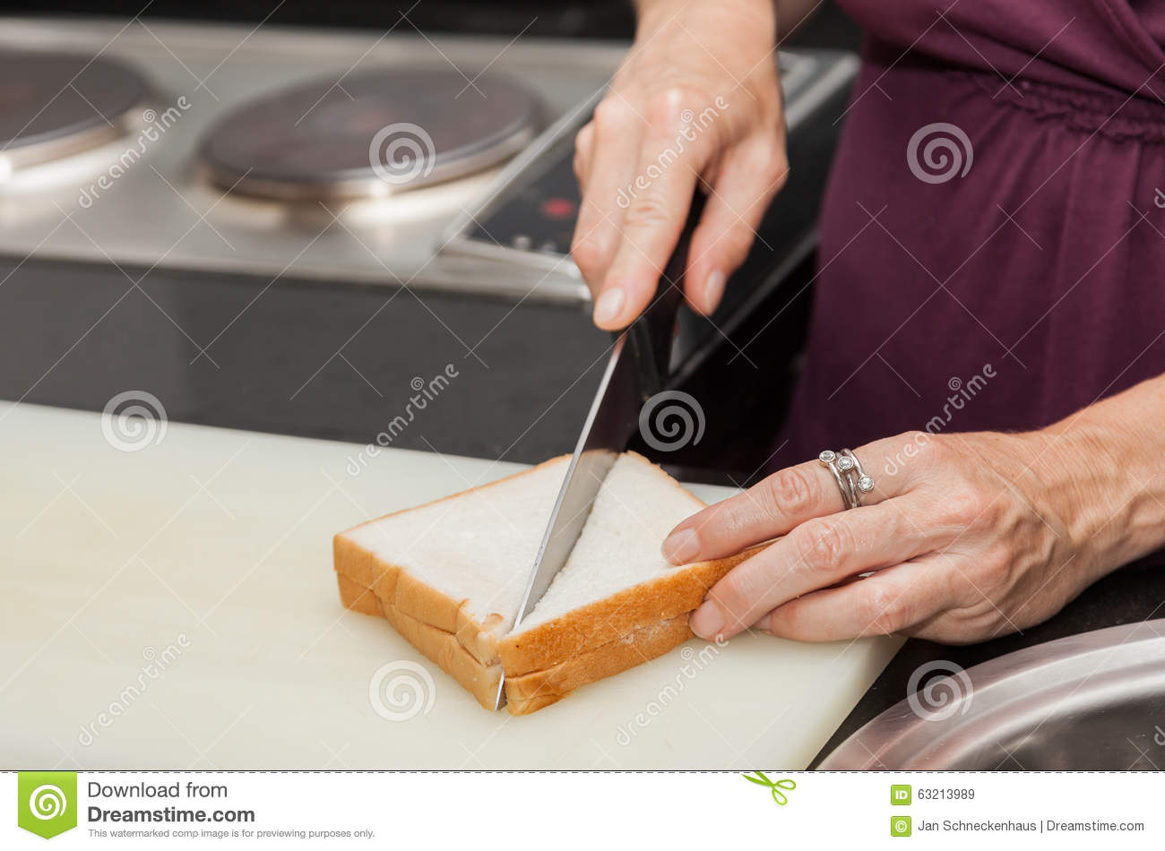 Closeup Of A Hand Which A Sandwich Cut With The Knife ...