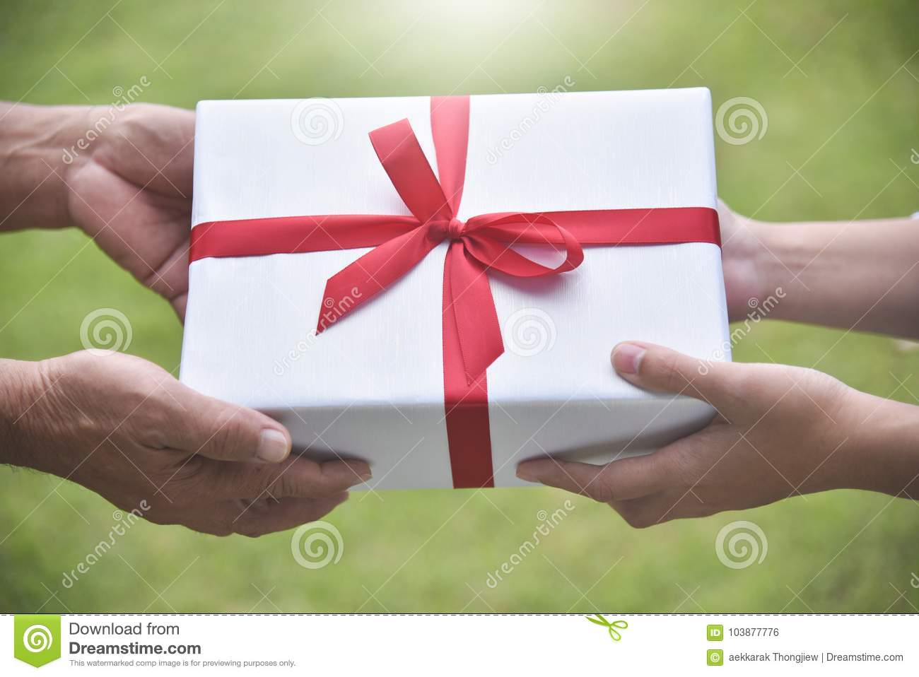 Closeup On Hands Asian Woman Giving A White Gift Box To Elderly Man