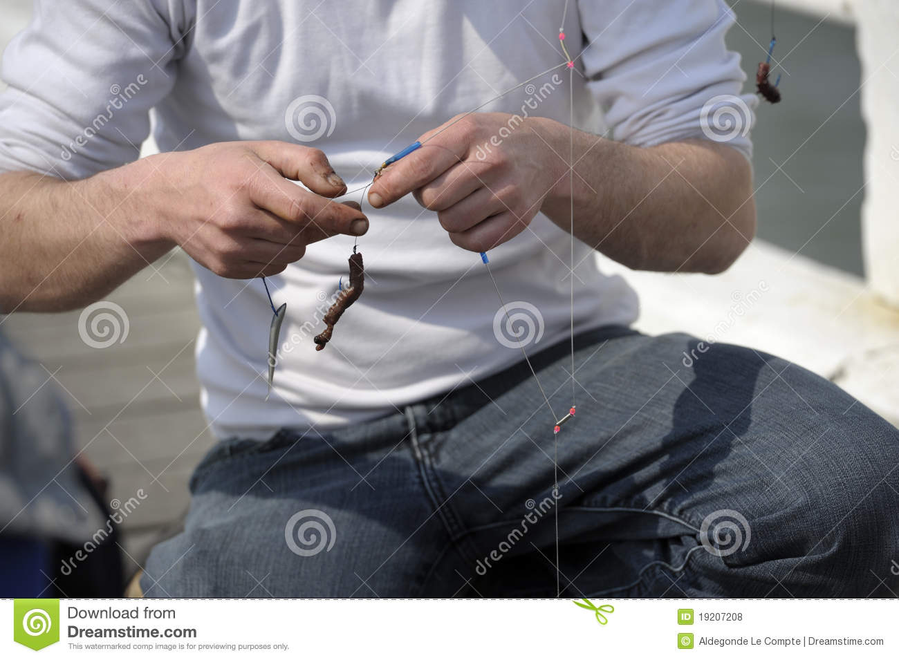Closeup on hands putting worm on fishing hook