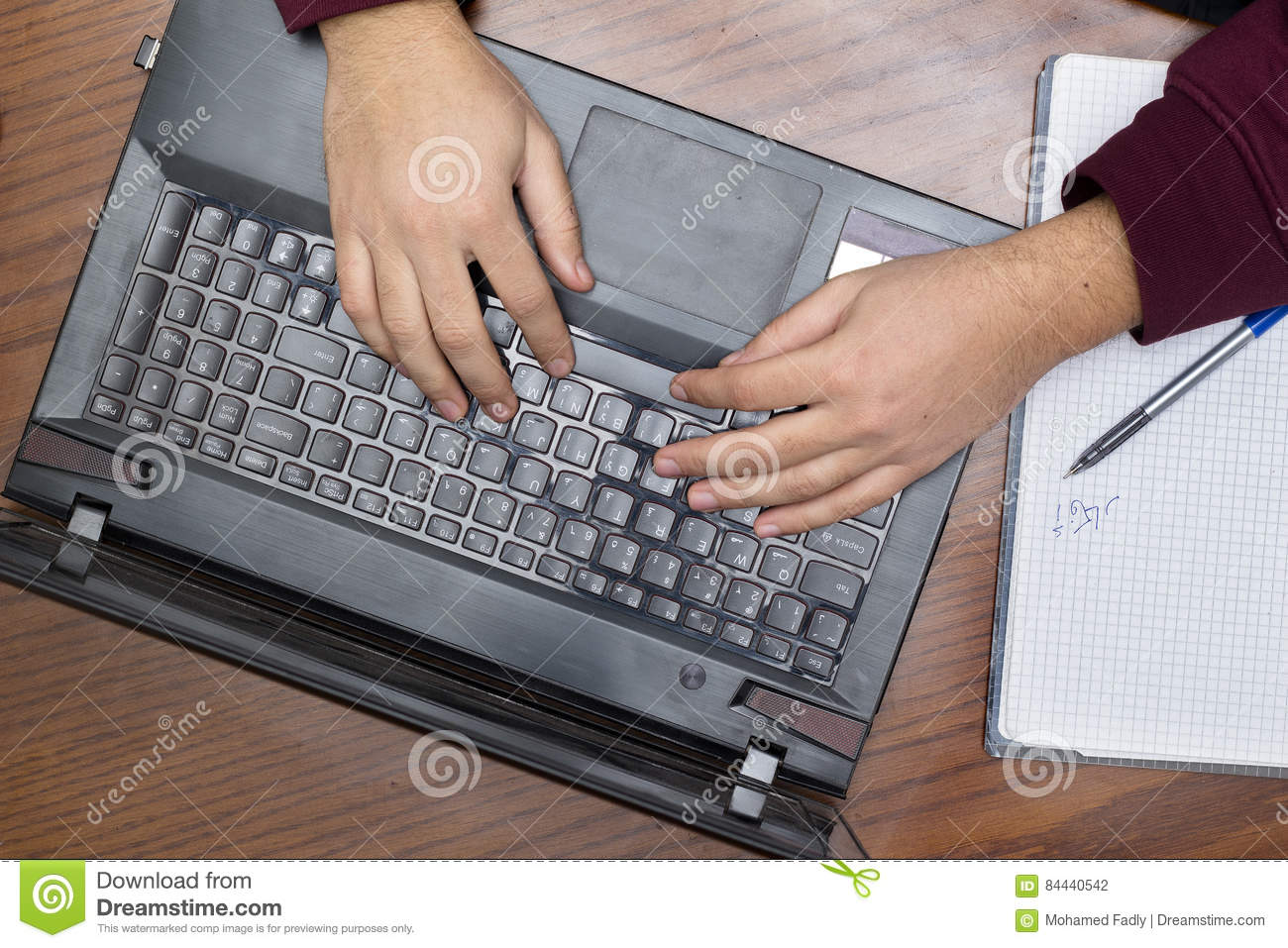 Closeup on Hands Typing on Keyboard, Notebook and Pen