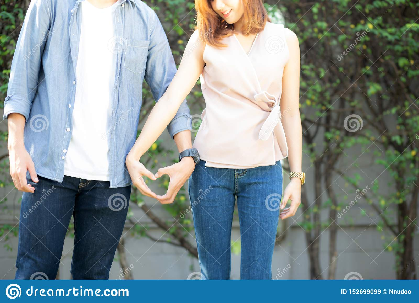 Closeup of happy couple fun making gesture heart shape with hand outdoor together