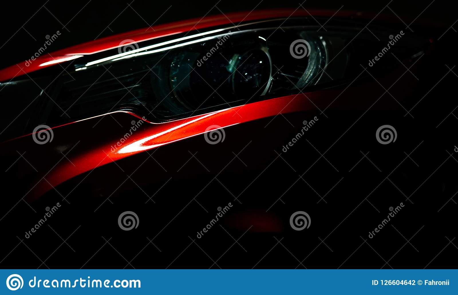Closeup headlight of shiny red luxury SUV compact car. Elegant electric car technology and business concept. Hybrid auto