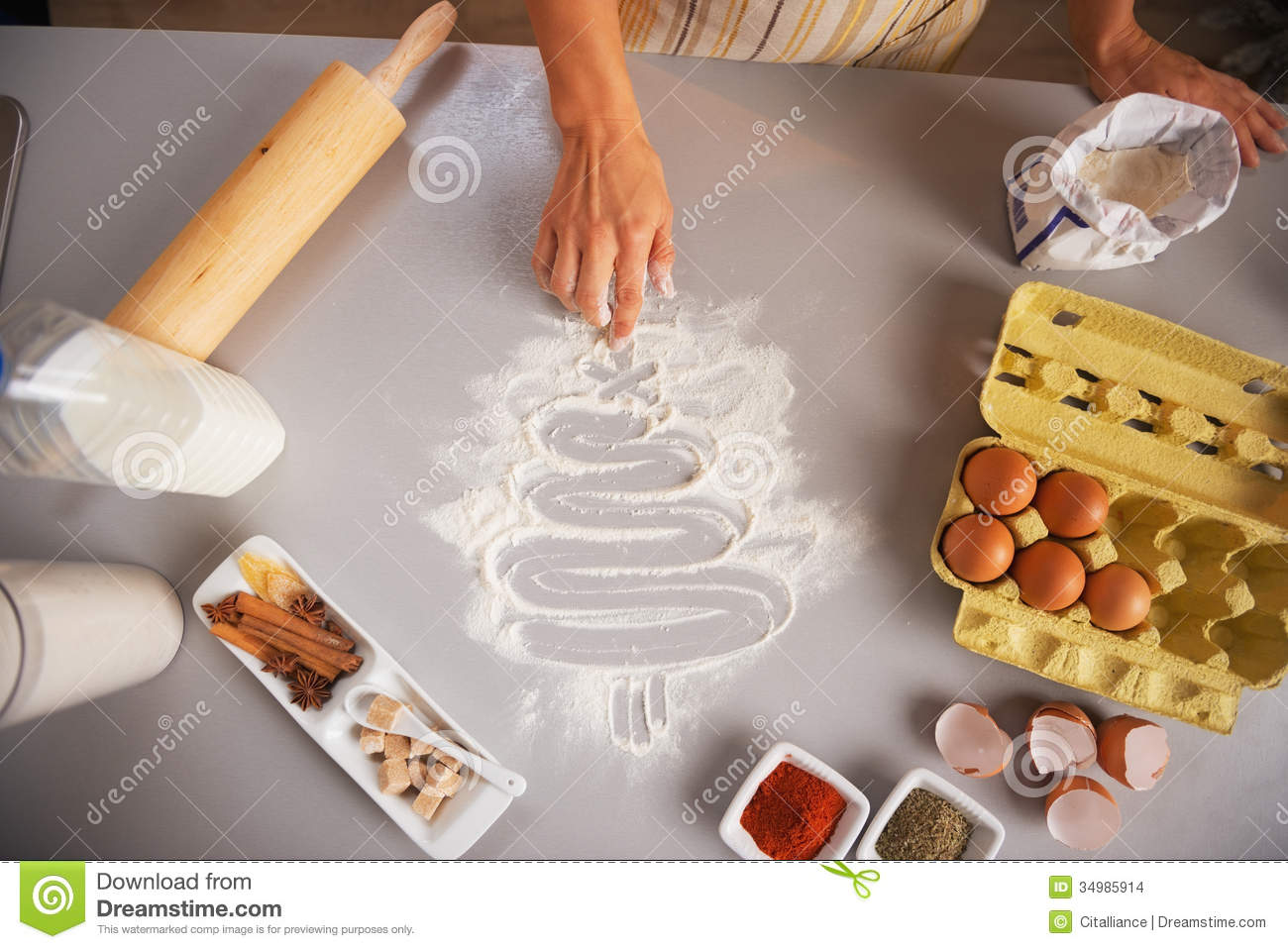 closeup on housewife drawing tree on kitchen table with flour